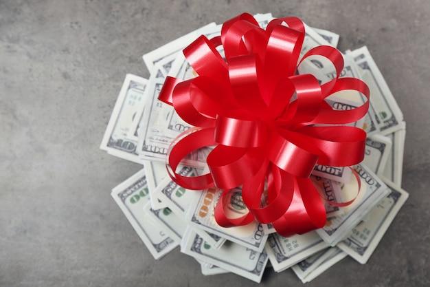 Stapel dollars met strik als geschenk op grijze ondergrond