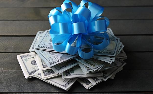 Stapel dollars met strik als geschenk op houten achtergrond