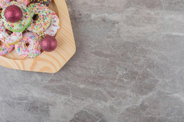 Stapel donuts en kerstballen op een houten schotel op marmeren oppervlak