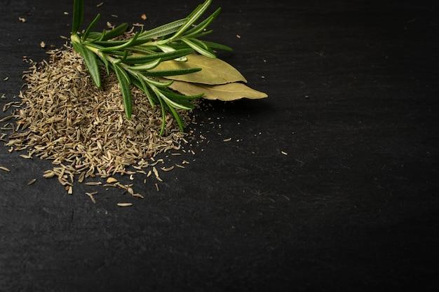 Stapel droge gehakte tijm. gedroogde geplette oreganobladeren. gemalen thymus kruiden, verse groene rozemarijn kruiden en specerijen close-up