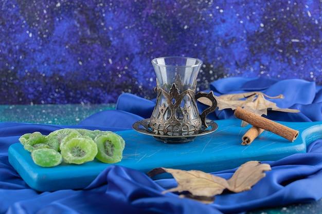 Stapel droge plakjes kiwi met theeglas en kaneel op een houten bord.
