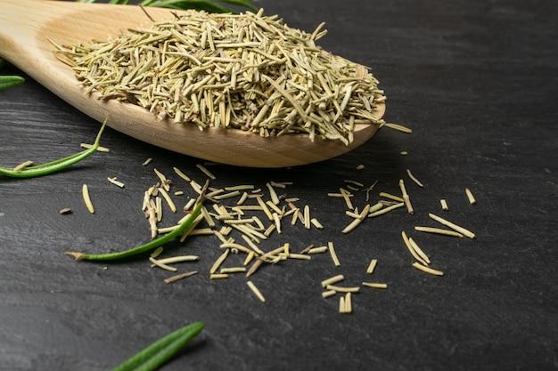 Stapel droge rozemarijnnaalden in lepel close-up. macro-opname van gedroogde gemalen en verse groene rozemarijn bladeren. gemalen kruiden, kruiden en specerijen op voedselleisteen