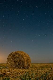 Stapel droog hooi onder de nachthemel met sterrenachtergrond