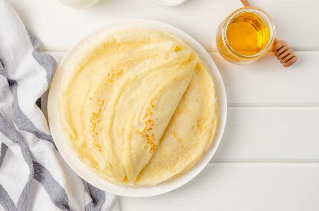 Stapel dunne pannenkoeken of pannenkoeken op een plaat met honing.