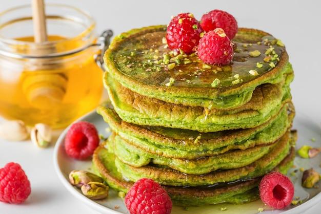 Stapel eigengemaakte pannekoeken met matchathee, verse frambozen, pistaches en honing. gezond ontbijtdessert