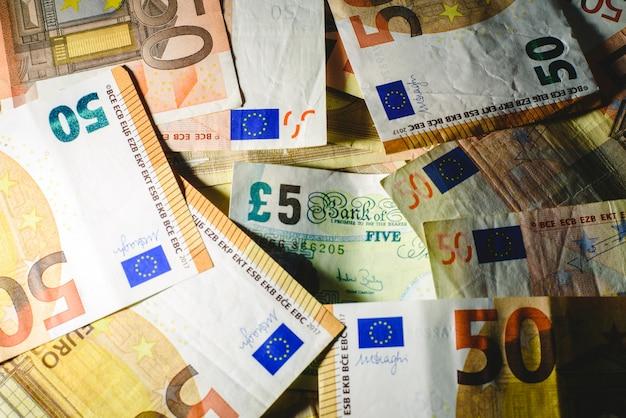 Stapel euro rekeningen die een pondnota in het nauw drijven door brexit.