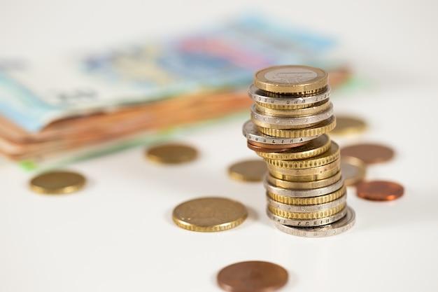 Stapel euromunten op tafel met aantekeningen op papier op achtergrond