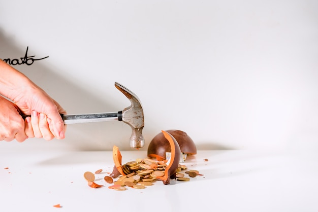 Stapel euromunten uit een spaarvarken verbrijzeld door een hamer.