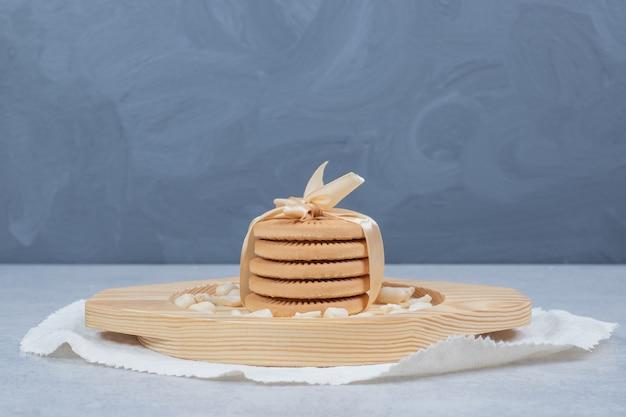 Stapel feestelijke koekjes en pinda's op houten plaat.