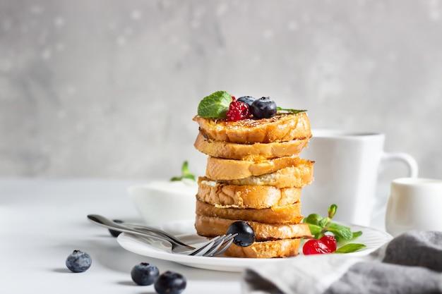 Stapel franse toast met bosbessen, gedroogde kersen, munt en koffie