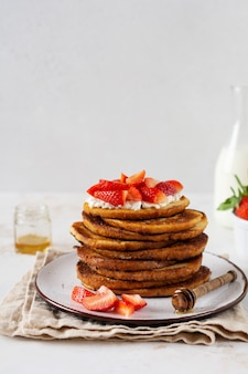 Stapel franse toast met kwark, honing en aardbeien voor ontbijt.