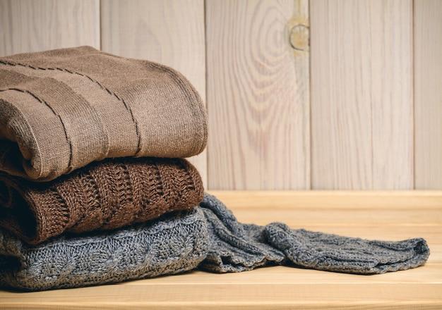 Stapel gebreide truien op een houten achtergrond