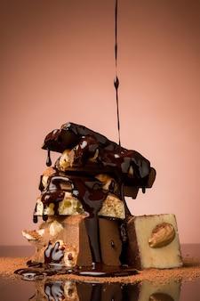 Stapel gebroken chocolade op tafel tegen bruine achtergrond en warme chocolademelk spray