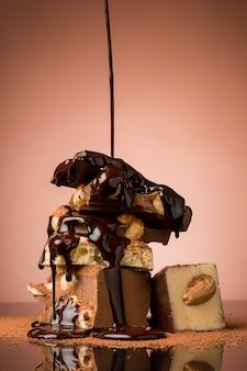 Stapel gebroken chocolade op tafel tegen bruine studioachtergrond en warme chocoladespray