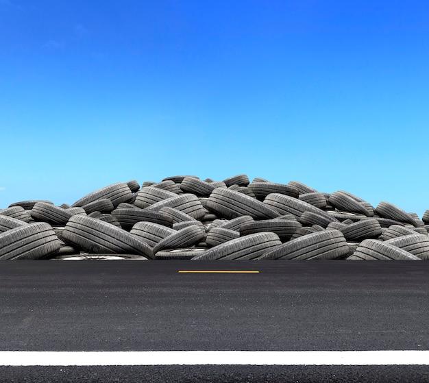 Stapel gebruikte rubberen banden op de weg met meer dan licht op blauwe hemelachtergrond