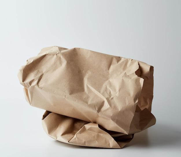 Stapel gedraaide bruine vellen papier op een wit oppervlak