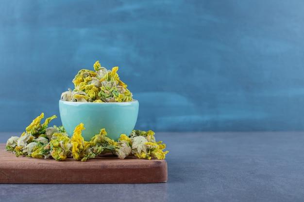 Stapel gedroogde bloemen op een houten bord en in kom.