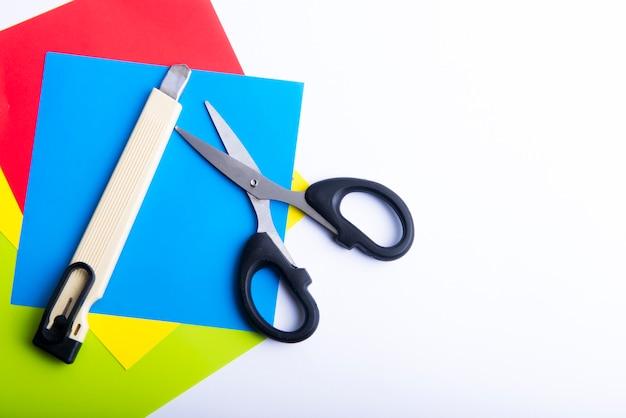 Stapel gekleurd papier met een schaar en mes geïsoleerd op witte achtergrond