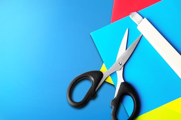 Stapel gekleurd papier met een schaar en mes met een blauwe achtergrond. terug naar school-concept