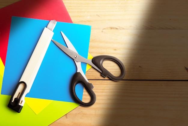 Stapel gekleurd papier met een schaar en mes met houten ondergrond
