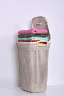 Stapel gekleurde handdoeken in de mand