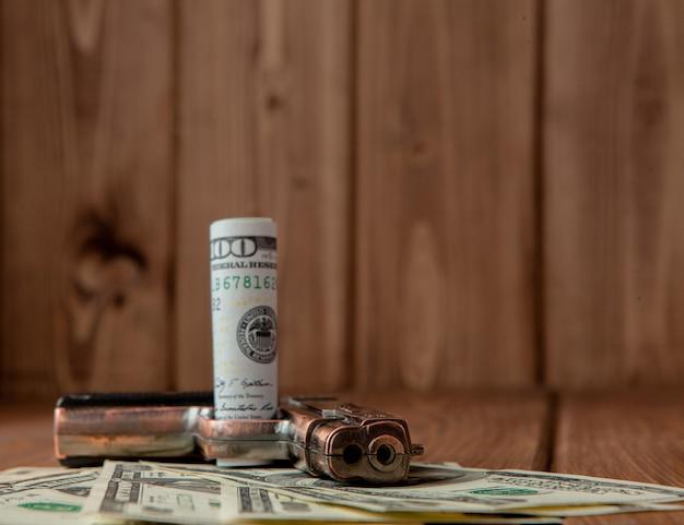 Stapel geld, drugs en een pistool op een houten tafel