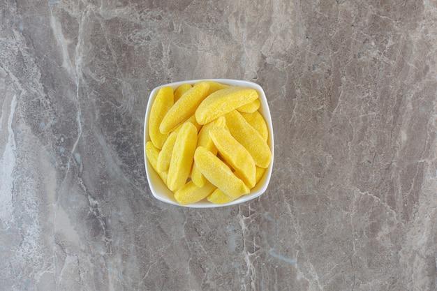 Stapel gele snoepjes in witte kom op grijze ondergrond. bovenaanzicht.