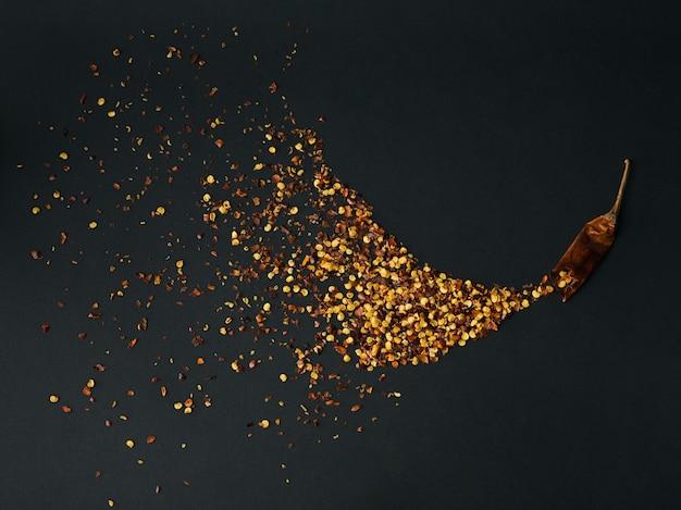 Stapel gemalen rode cayennepeper, gedroogde chilivlokken en zaden op een zwarte. zelfgemaakte kruideningrediënten om te koken.