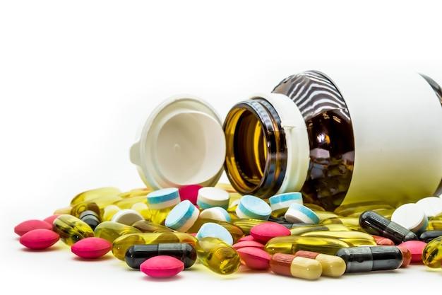 Stapel geneeskunde pillen en drug capsules met pil flessen op witte achtergrond.