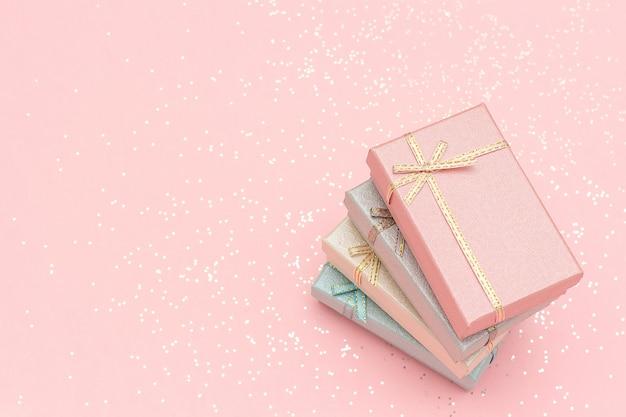 Stapel geschenkdozen met pastelkleuren op roze, bovenaanzicht
