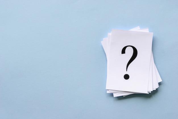 Stapel gestapelde vraagtekens op wit papier