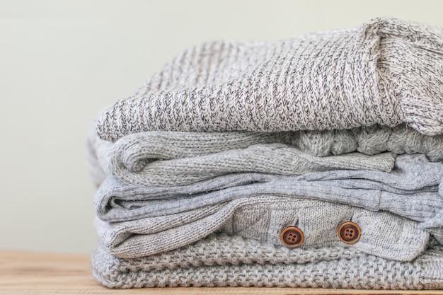 Stapel gezellige grijze truien voor de koude herfst op houten tafel.