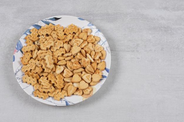 Stapel gezouten crackers op kleurrijke plaat.