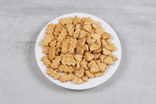 Stapel gezouten crackers op witte plaat.