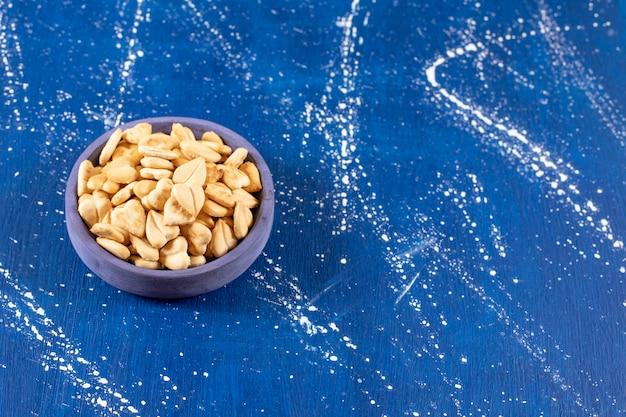 Stapel gezouten hartvormige crackers geplaatst in blauwe kom