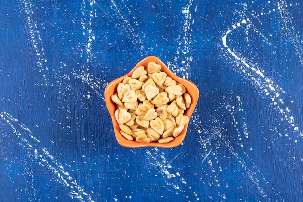 Stapel gezouten hartvormige crackers geplaatst in oranje kom