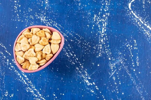 Stapel gezouten hartvormige crackers geplaatst in roze kom