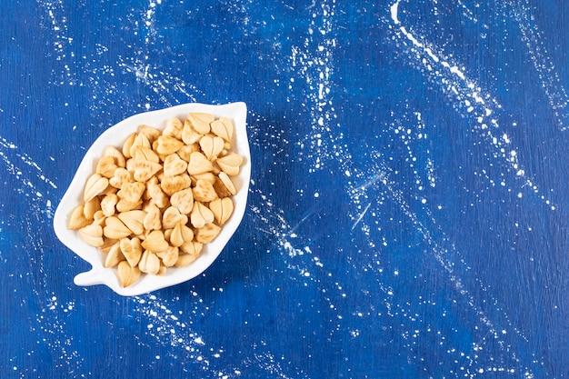 Stapel gezouten hartvormige crackers geplaatst op bladvormige plaat.