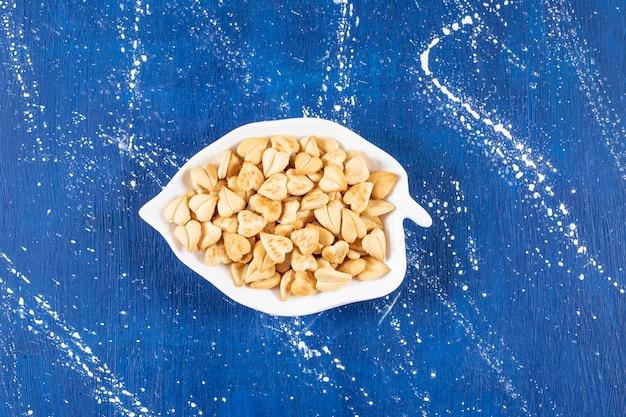 Stapel gezouten hartvormige crackers geplaatst op bladvormige plaat