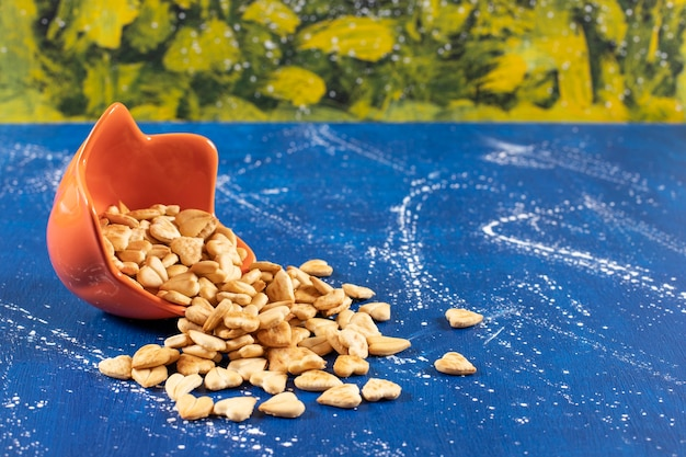 Stapel gezouten hartvormige crackers geplaatst uit oranje kom.