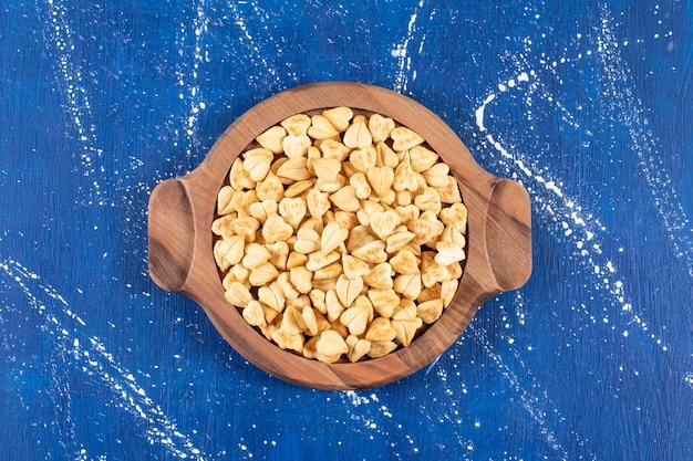 Stapel gezouten hartvormige crackers op een houten bord geplaatst.