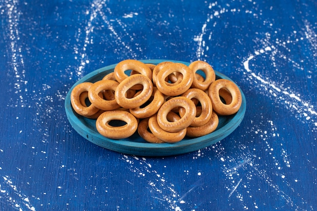 Stapel gezouten ronde pretzels geplaatst op blauw bord