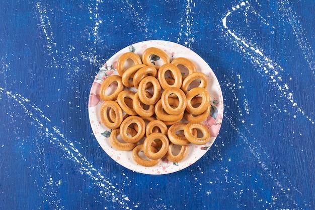 Stapel gezouten ronde pretzels geplaatst op kleurrijke plaat.