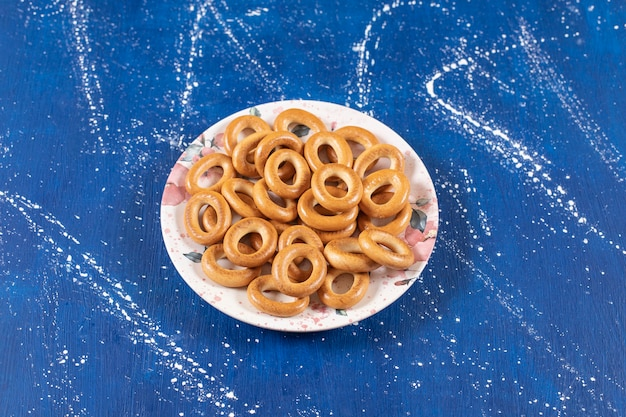 Stapel gezouten ronde pretzels geplaatst op kleurrijke plaat