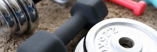 Stapel glanzende chromen halters schijven liggen rond grip thuis tapijt als binnenlandse sport oefeningen tijdens coronavirus quarantaine periode close-up
