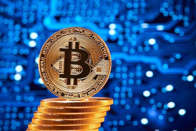 Stapel gouden bitcoins met één bitcoin op zijn rand die op vaag blauw circuit wordt geplaatst.