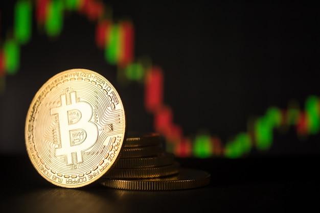 Stapel gouden munten met bitcoin symbool met voorraad grafiek achtergrond.