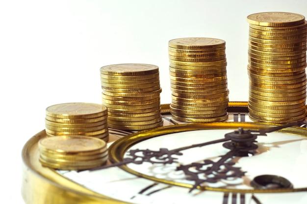 Stapel gouden munten op de vintage klok