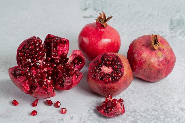 Stapel granaatappels. gesneden of hele granaatappel op grijze ondergrond.