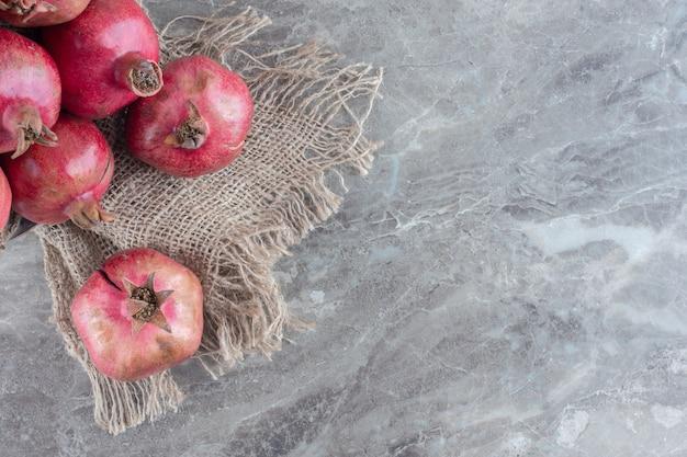 Stapel granaatappels op een stuk doek op marmer.